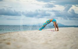 woman playing yoga pose on sand beach