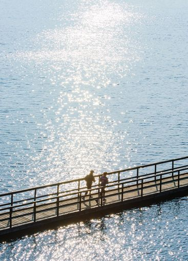 Two people running on bridge over water, high angle