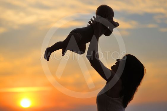Woman with little baby as silhouette