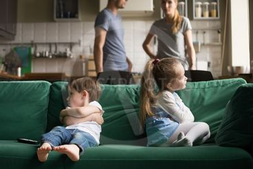 Upset offended brother and sister sitting on couch