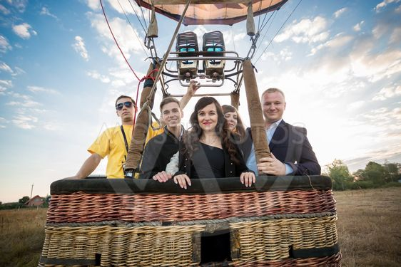 group of people posing in hot air balloon basket
