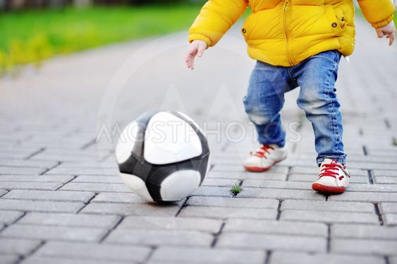 Little boy having fun playing a soccer game on sunny...