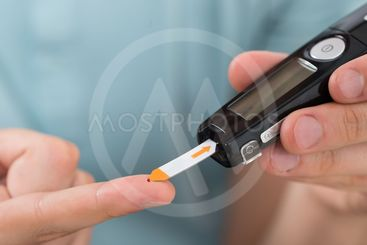 Man Using Glucometer To Check Blood Sugar Level