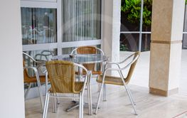 Metal tables and chairs with wicker seats in outdoor cafe.