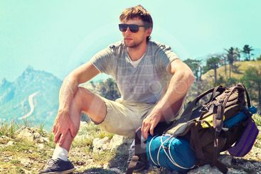 Young Man Traveler with backpack relaxing on Mountain...