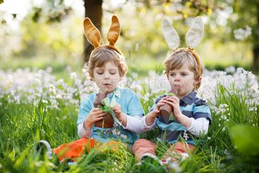 Two little boys wearing Easter bunny ears and eating...