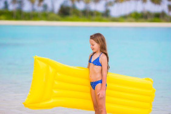 Adorable little girl with air inflatable mattress during...