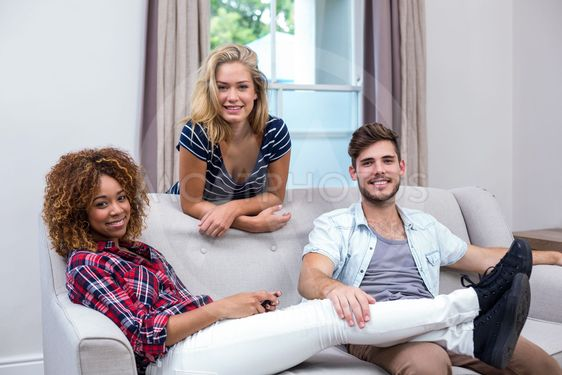 Happy multi-ethnic friends relaxing at sofa