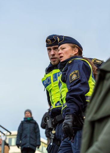 Polisman och poliskvinna övervakar demonstration.