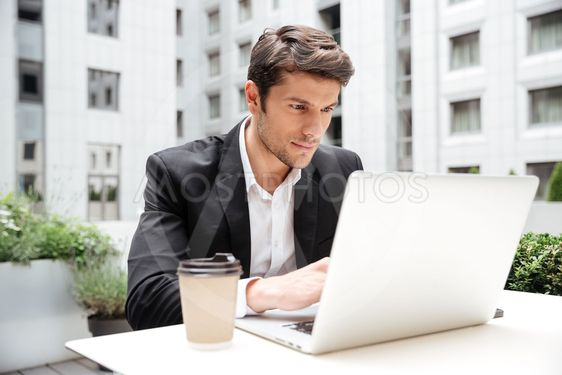 Businessman using laptop in outdoor cafe
