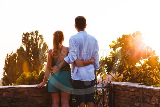 Young couple enjoying sunset on their travel