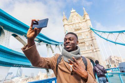 Man taking selfie in London with Tower Bridge on background