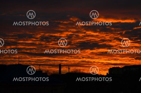Orange dramatic city sunset. Dawn fire in the sky over a...