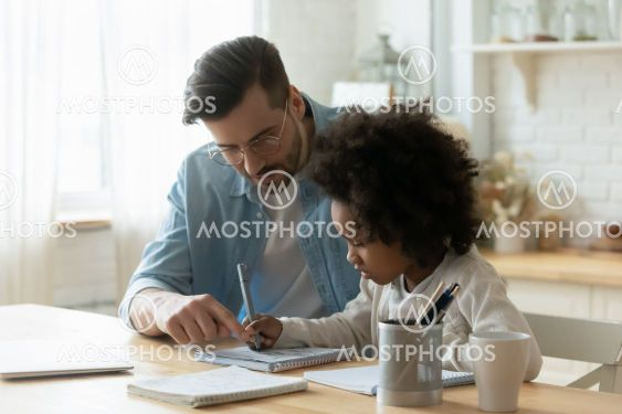 Male tutor helps understand arithmetic task to little...