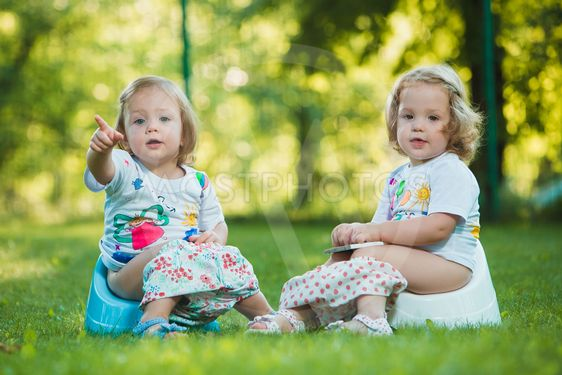 The two little baby girls sitting on pottys against green...