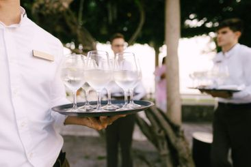 The waiter spreads cold water with lemon on the tray.