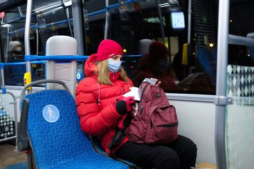 A woman in a medical mask in a red jacket and a hat sits...