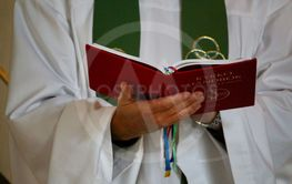 Präst läser ur kyrkohandboken