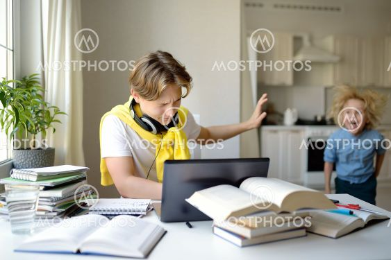 Teenager boy study at home. Online education and...