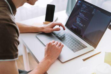 Young man mobile developer, programmer writes program...