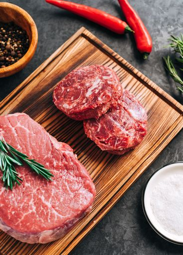 Raw beef steak and minced round steak for burgers on...