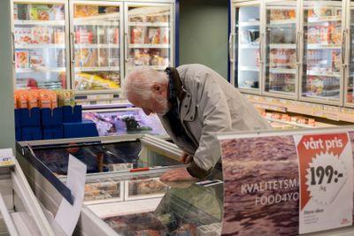 Pensionär letar matvaror i frysdisken.