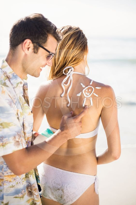 Man making a sun symbol on womans back while applying a...