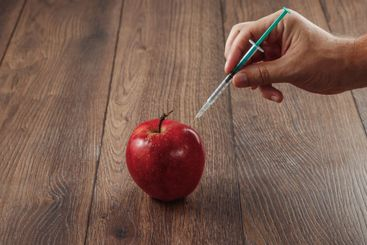 Red apple injecting a needle or syringe and chemical...