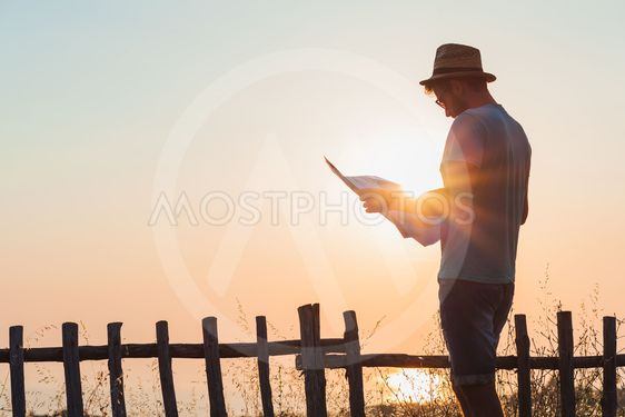 Young hipster man exploring map over the sunset at seaside