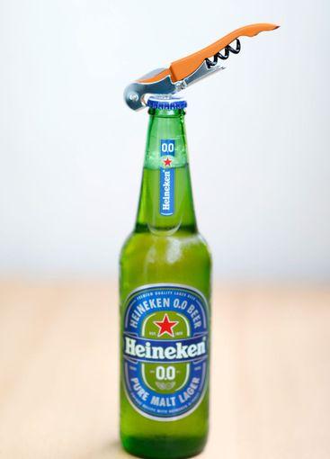 Green glass Heineken beer bottle and bottle opener