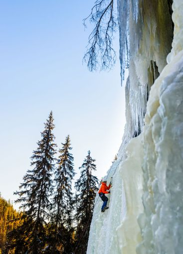 Mountain climber going up on snowy slope with axes
