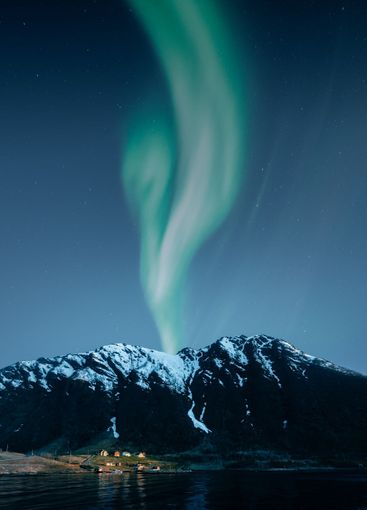 Aurora borealis and mountain landscape with small...