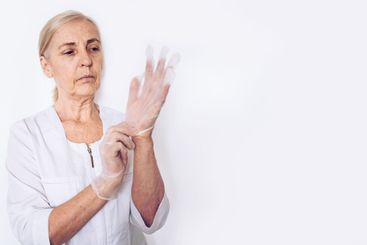 Elderly mature woman doctor or nurse in a white medical...