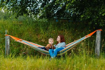 Happy mother and son sitting on the hammock