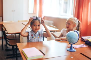 Two schoolgirls are sitting at a school desk, back to...
