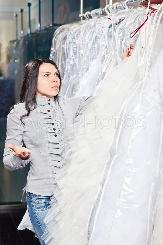 Beautiful girl chooses her wedding dress.  Portrait in...