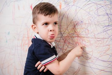 The boy draws on the wall and grimaces. The child is...