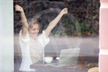 Portrait of happy woman in coffee shop celebrating...