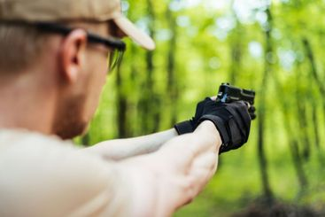 instructor with gun in forest leads aiming and posing on...