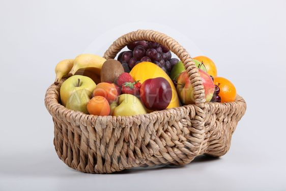 Wicker basket full of fresh fruit at a slight angle
