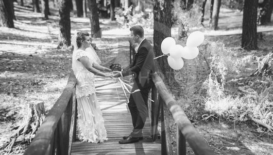 Black and white photo of happy bride and groom holding...