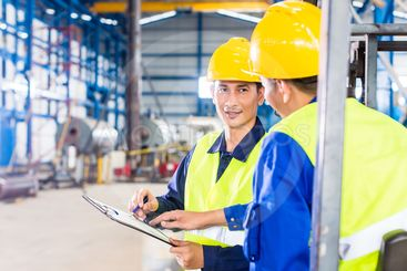 Worker and forklift driver in industrial factory