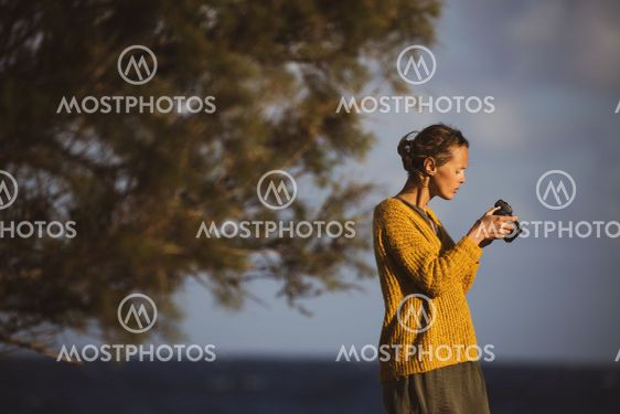 Pretty, young woman with a mirrorless camera, taking...