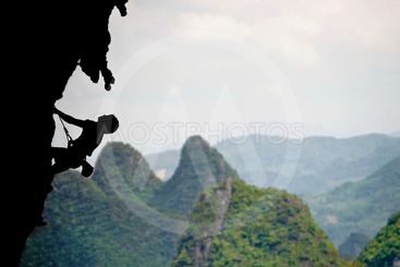 Climbing a steep rocky cliff