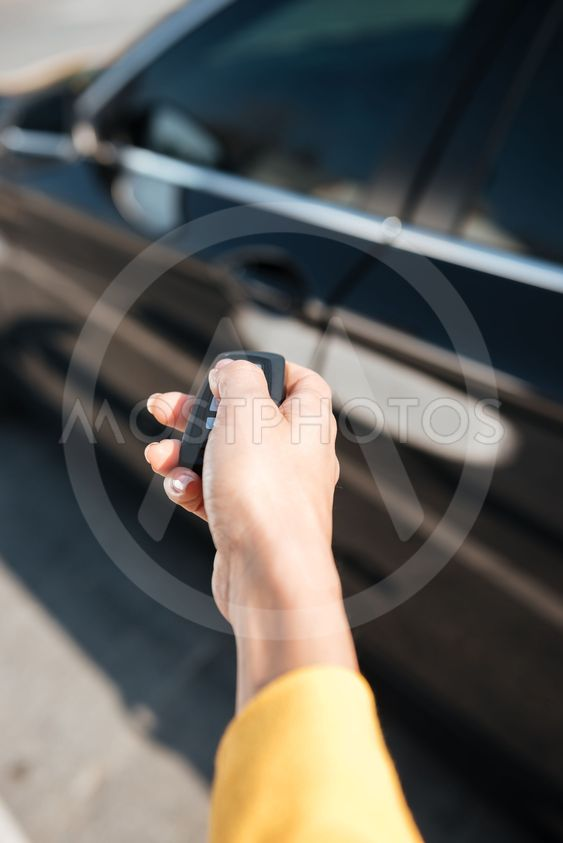 Woman hand holding keys and closing door of her car