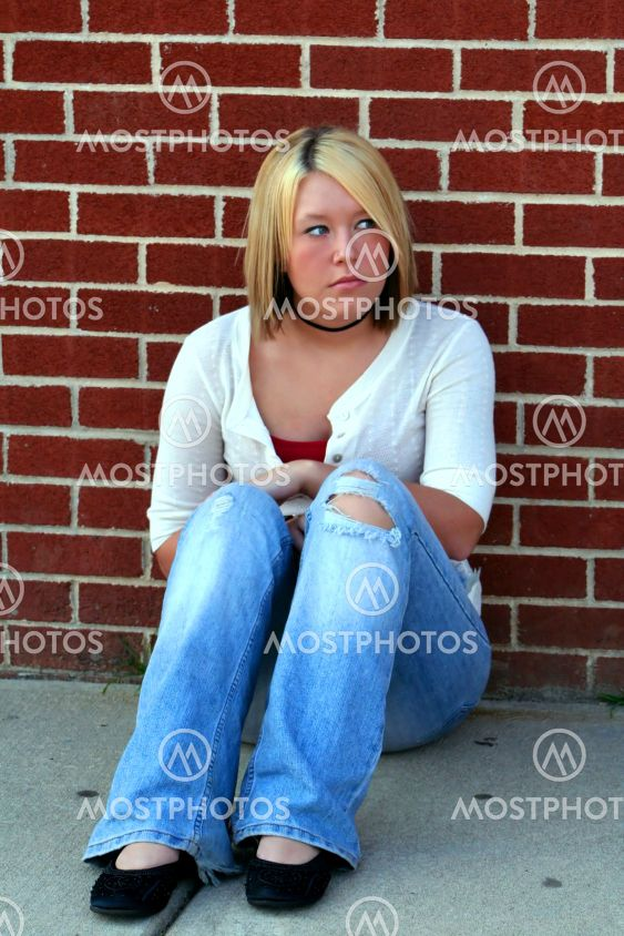 Cautious Blond Sitting By The Brick Wall