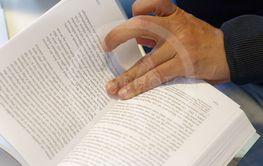 Närbild på elevs hand när han läddrar i studielitteratur