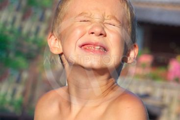 Child Boy making sore crying Faces showing Calf's Teeth...