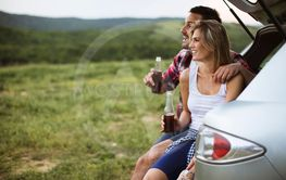 Loving couple sitting in the car trank during trip in...