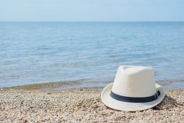 A white straw hat lies on the sand by the water. Sea...